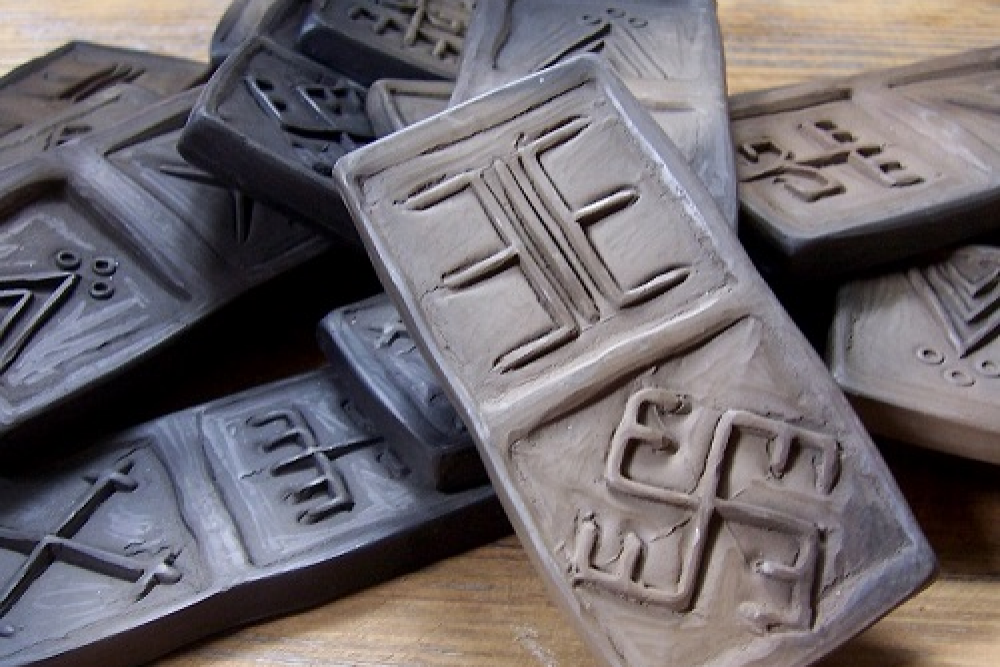 Latgolā nu muola teik veiduota domino spēle ar latvju rokstu zeimem
